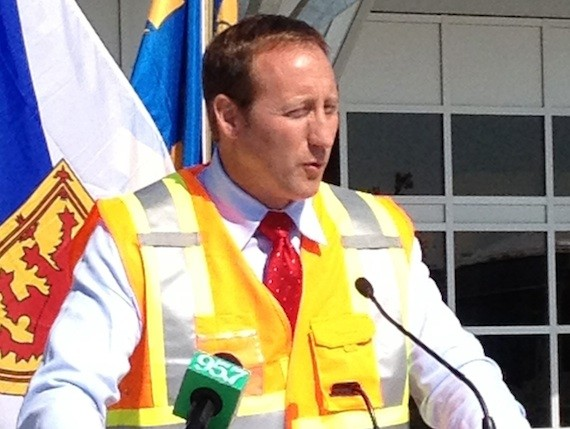 Peter MacKay wears an unattractive bright yellow construction vest at a media event in 2012.