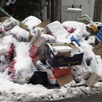 Snow-covered garbage bags, a mix of black and white colours on a city street.
