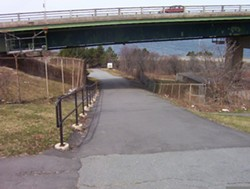 The Seaview Lookoff Trail travels under the bridge. The cable abutment is to the right, beyond the fence.