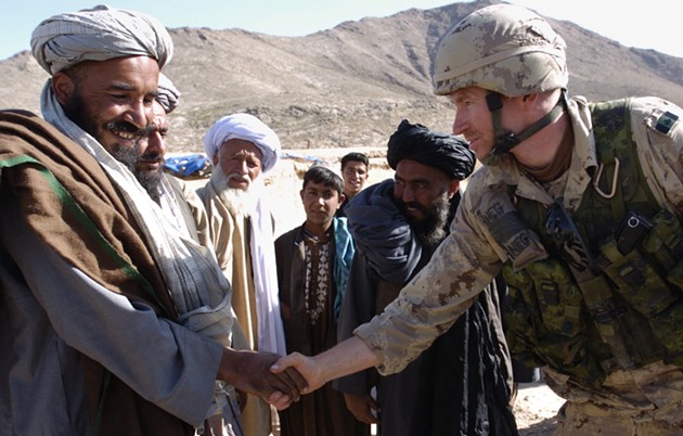 Trevor shaking hands with Afghan locals. - SUBMITTED