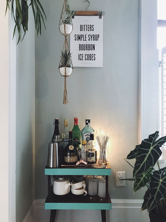"""""""Our bar was just a little shitty TV table of fake wood, like every side table in the '70s was made of, that I spied in the garbage room at my friend's apartment. I sanded down the sides, toll painted the sides minty green, a friend made that old fashioned print and we built a little bar around it."""""""