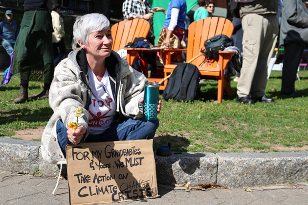 Kelly Daphne sits on the ground before the rally. She is attending to support a future for her grandchildren. - ISABEL BUCKMASTER