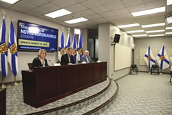 After: Community services minister Kelly Regan joined premier Stephen McNeil and Robert Strang at the Thursday, March 19 briefing. The bottle of hand sanitizer at right is one of the only attendees. - COMMUNICATIONS NOVA SCOTIA