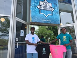Marvin Okello and Birt Beal show off a t-shirt outside the Quinpool Road Wanderers store. - HFX WANDERERS FC
