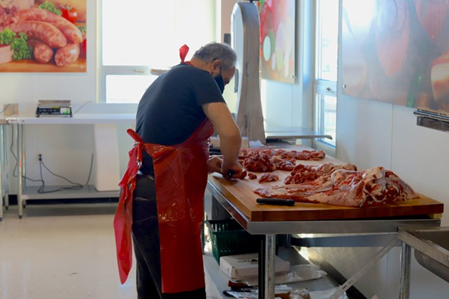A butcher divides halal meat at Syriana Market the day before their grand opening. - VICTORIA WALTON