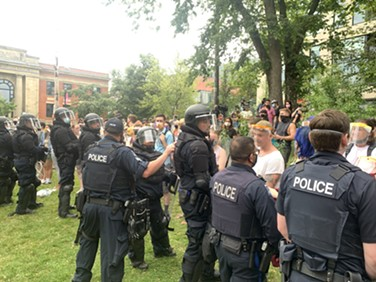 Police push back against protesters on the old library lawn Wednesday. - THE COAST