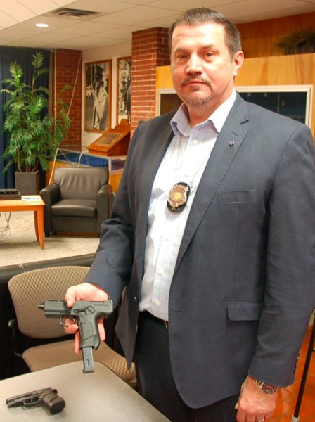 """Detective sergeant Darrell Gaudet holds one of the """"toy"""" replica guns. - THE COAST"""