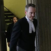 Riley's attorney, Trevor McGuigan, entering court.