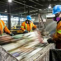 Workers sort through the trash at the Otter Lake Landfill.