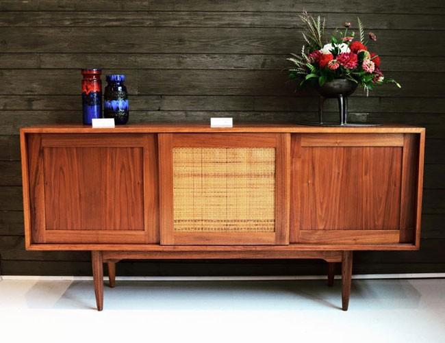 Refinished walnut credenza, featuring three sliding doors, adjustable/removable shelving, weave centrepiece, and tapered legs. - VIA FACEBOOK