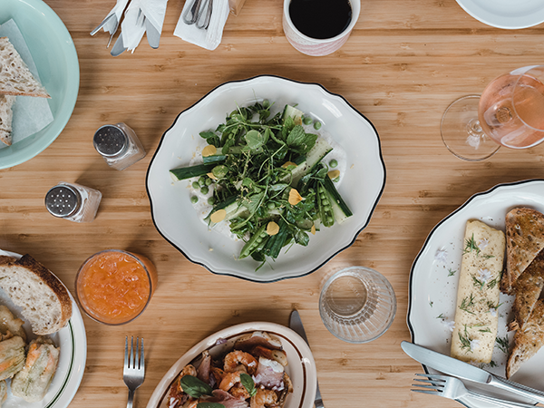 Clockwise from left: Adamski's zucchini blossom poppers, cucumber and peashoot salad with garam masala yogurt, classic three-fold French omelette with gruyere and herbs (and Birdie's Bread Co. sourdough) and shrimp toast. - ALEXA CUDE
