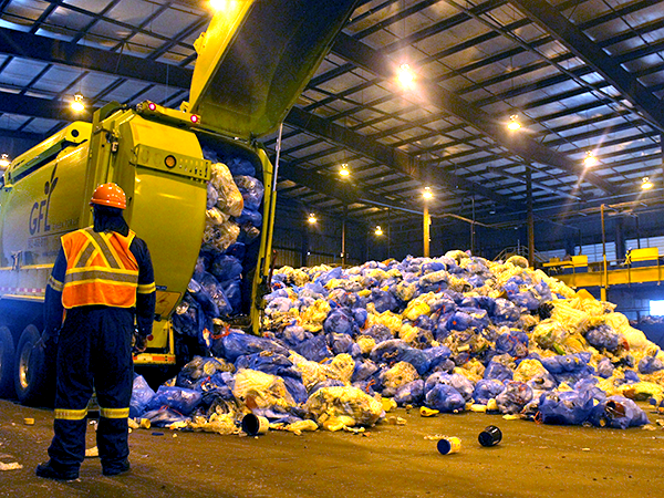 Recycling trucks dump blue plastic bags at the MRF in Bayers Lake. - VICTORIA WALTON