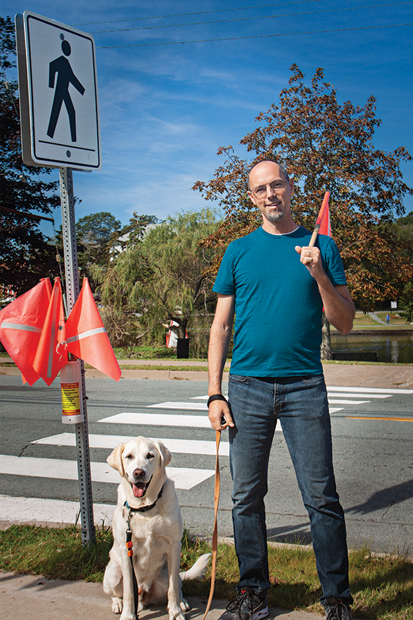 Matt Spurway (above) walks Ajax using flags like those installed near 3D crosswalk in Dartmouth. - SUBMITTED
