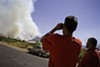 Abel Guerrero and Jesse Pacheco gaze at the smoke plumes caused by the Monument fire as it advances into Hereford, Ariz.