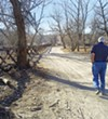 Alex Mills walks along the bed of the Santa Cruz River.