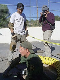 LEO W. BANKS - Border Patrol agent Tom Pittman and two National Geographic crewmen prepare to enter a parking-lot tunnel in downtown Nogales.