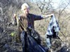 Edith Lowell holds garbage from the illegals' dump site off her driveway, including burlap used to wrap drug bundles.