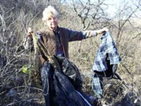 LEO W. BANKS - Edith Lowell holds garbage from the illegals' dump site off her driveway, including burlap used to wrap drug bundles.