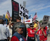 """MARI HERRERAS - No on Prop 200 volunteers Caitlin Jensen and Murray Hudson - (holding the sign) were met by two women at the Oct. 10 Tucson Tea - Party who followed them through the ballpark, shouting, """"ACORN coming - through."""""""