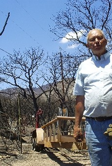 Retired teacher Larry Kastens stands amid the rubble of his home in Ash Canyon.