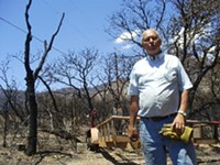 LEO W. BANKS - Retired teacher Larry Kastens stands amid the rubble of his home in Ash Canyon.