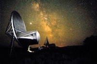 COURTESY OF SETH SHOSTAK - SETI's Seth Shostak took this picture of an Allen telescope using a four-minute exposure. Notice the Milky Way in the sky, Jupiter above the scope and the shadow of Shostak's legs below the telescope.