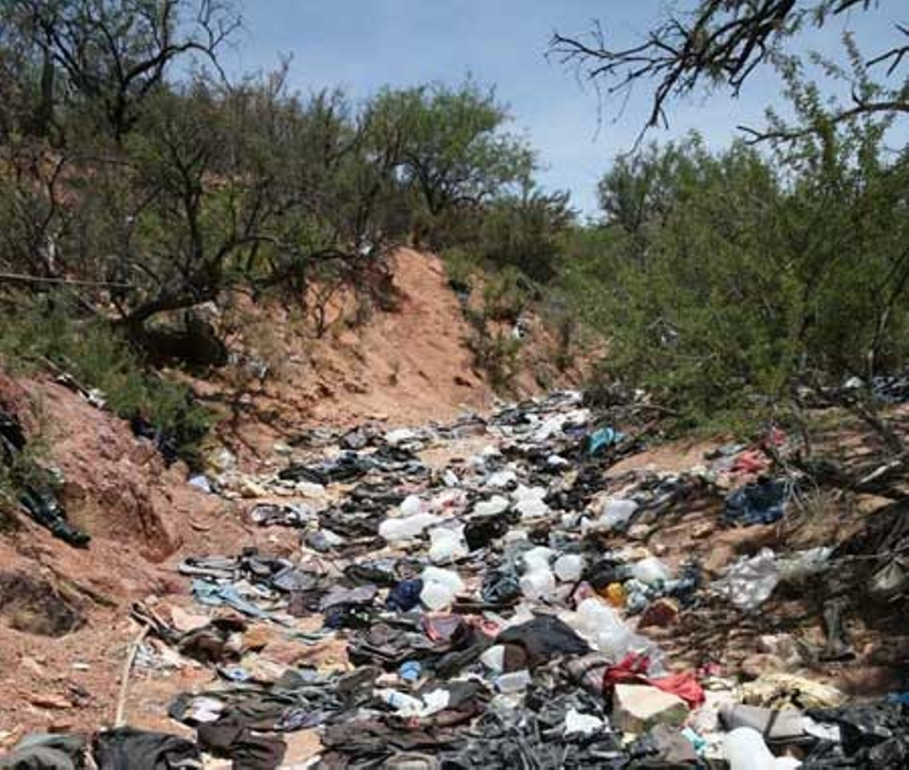 LEO W. BANKS - This trash-filled wash is below Diablito Mountain, about 5 miles - west of Interstate 19, southwest of Arivaca Junction. It is 21 miles - north of the border at Nogales. The illegal aliens who dump their trash - here have just emerged from the Tumacacori Highlands, which are also - trashed out.