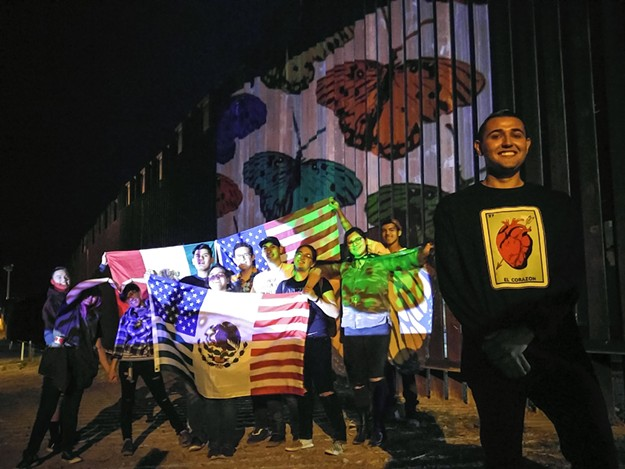 High school students from Tucson and teacher posing by art projected on the U.S.-Mexico border at Nogales, Arizona. - PHOTO BY RAECHEL RUNNING, COURTESY OF ERNESTO SOMOZA