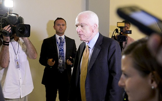 Sen. John McCain, R-Arizona, walks past reporters in a hallway outside his Washington office in July, just hours after his early-morning vote helped kill the latest attempt to repeal and replace Obamacare. - BEN MOFFAT/CRONKITE NEWS