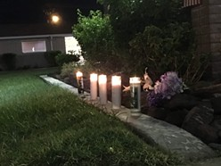 Flowers and candles were placed outside the Phoenix funeral home where the body of Sen. John McCain was taken from his home in Cornville. - CHRIS MCCRORY/CRONKITE NEWS