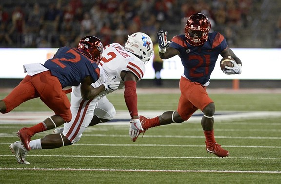 Arizona running back JJ Taylor tries to outrun University of Houston safety Khalil Williams during last year's 19-16 victory by the Cougars in Tucson. - ARIZONA ATHLETICS