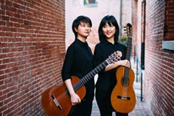 Meng Su (left) and Yameng Wang (right) posing with their guitars. - COURTESY