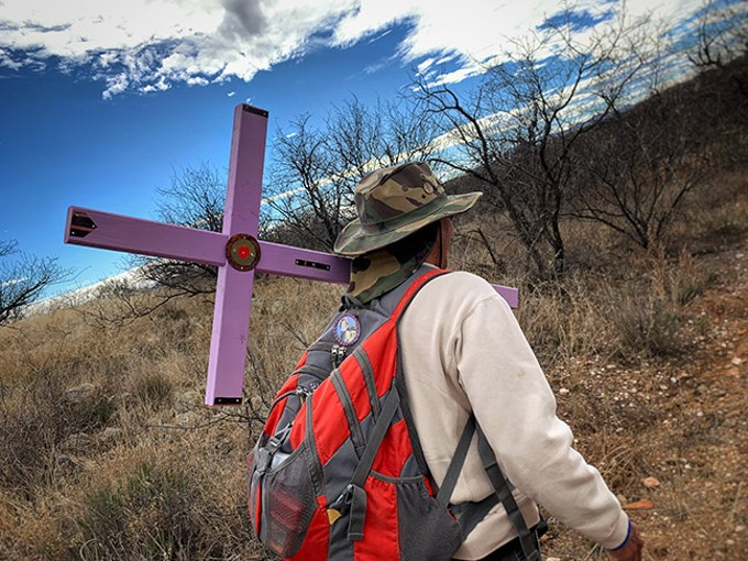 Andre Rivera carries a cross to a death site. - PHOTOS BY BRIAN SMITH