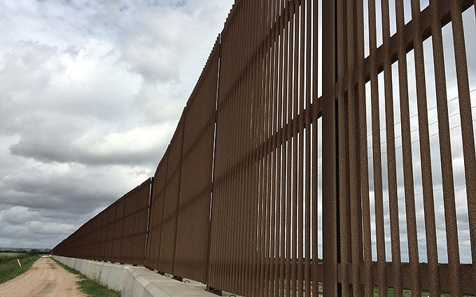 """A border wall already runs up to both sides of the River Bend Resort & Golf Club in Brownsville, Texas. Erected in 2006, this part of the wall stands 18 feet and ends abruptly along a busy highway, leaving a gap several miles wide. Much of the most-recent border wall construction has been in Texas and California."" - PHOTO BY MINDY RIESENBERG 