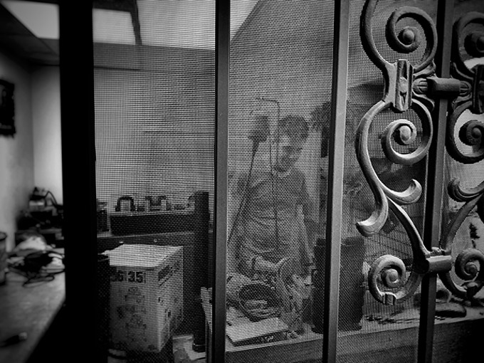 Patrick Carey at work behind the screen door of his tiny silversmithing and lapidary studio. - BRIAN SMITH