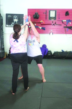 Instructor Tylar Elin Zinn demonstrates a self-defense move to disarm an attacker inRising Phoenix Fitness & Defense's old location. - JAMIE VERWYS