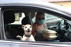A service industry worker and her dog pick up a couple of La Cocina's to-go meals. - PAT FOLEY