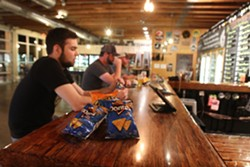 Employee Ben McBride has a quick beer after his shift on Sunday, May 10 helping get the Arizona Beer House stocked and ready to open for dine-in service. - AUSTIN COUNTS