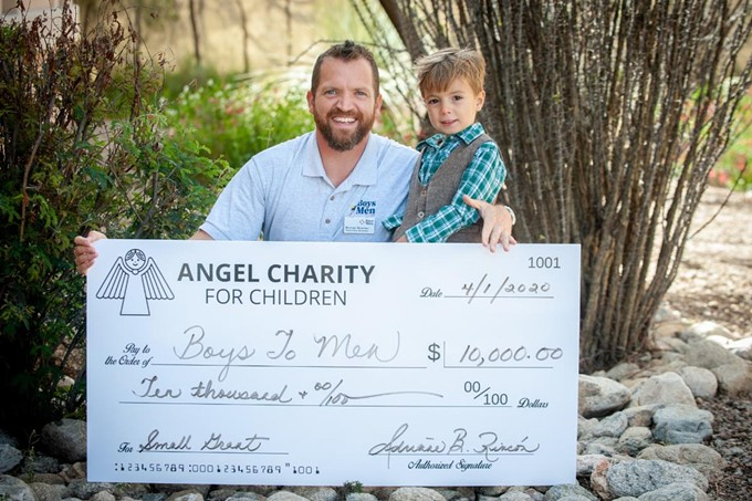 Boys to Men Executive Director Michael Brasher and his son holding their $10,000 check from Angel Charities - COURTESY PHOTO