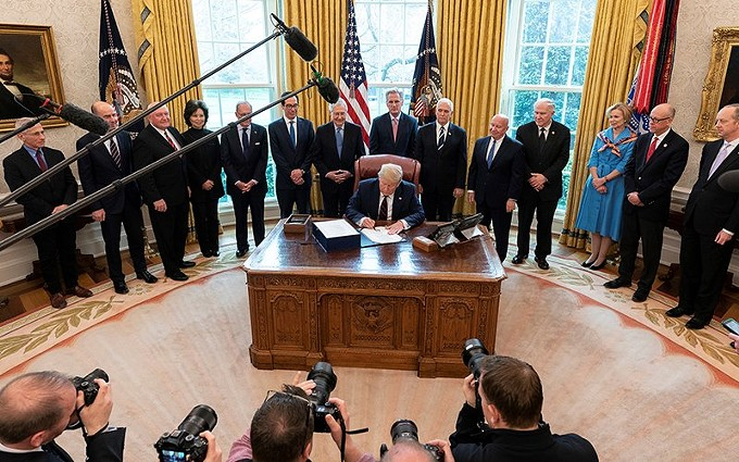 President Donald Trump signs the Coronavirus Aid, Relief, and Economic Security – CARES – Act in March. The $2.2 trillion economic stimulus package includes funds for businesses and individuals affected by the fallout from COVID-19, but Latinos say they are not seeing the money. (Photo by Shealah Craighead/The White House)