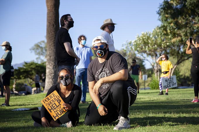 """Leigh-Ann Salazar and Tanner Childress sit and wait amongst their fellow Black Lives Matter protesters at Catalina Park, located at 941 4th Ave., on July 4, 2020. This was Childress' first BLM protest and Salazar's third. """"I went to the protest in Huntington Beach, Phoenix and now this one,"""" Salazar said. """"What makes this different is that, I've lived here for three years now and this is my home. This is where I met my boyfriend. My life is here."""" - ALAN SCOTT DAVIS"""