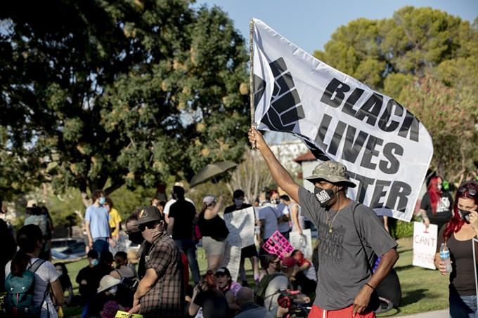 Robert Williams, 47, a veteran with the U.S. Air Force, waves a Black Lives Matter flag at Catalina Park during the Black Lives Matter protest in Tucson, Ariz., on Saturday, July 4, 2020. - JOHN DE DIOS