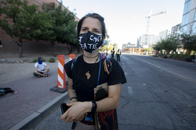 """Lily Pavy, 24, dons an """"I can't breathe"""" mask during the rally, a call back to the last words uttered by George Floyd before he was killed by former Minneapolis police officer Derek Chauvin. Pavy, who works at the Tucson Wildlife Center, found out about the rally through Social Media said, """"I'm glad to see people take the Fourth of July to come out and fight for what they believe in."""" - JOHN DE DIOS"""