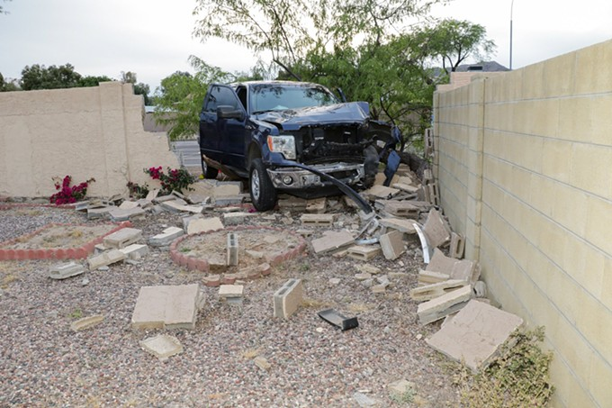 """Homeland Security Investigations agent Richard Mortensen's blue Ford F-150 stopped atop a toppled tree and concrete debris in a backyard in Ahwatukee Foothills. The truck careened into a concrete wall during a """"pinch maneuver"""" as agents were attempting to stop a suspect vehicle. (Crime scene photo: Phoenix Police Department)"""