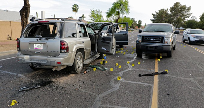 Warren Jose's bullet-riddled Chevrolet Trailblazer faces two Homeland Security Investigations trucks, as viewed looking south. (Crime scene photo: Phoenix Police Department)