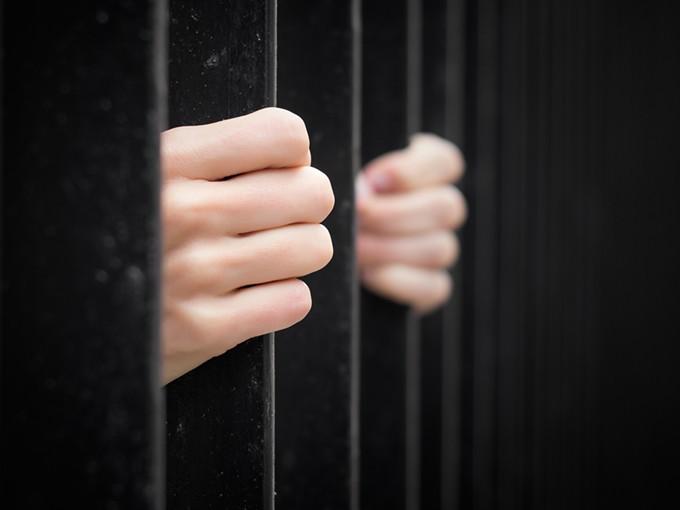 bigstock-prisoner-behind-jail-bars-73500814.jpg