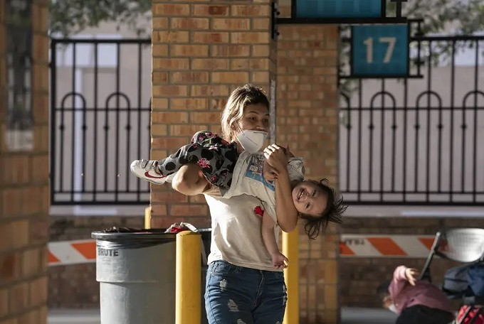 A Central American asylum seeker carries her child at a bus station in Brownsville, Tex. - VERÓNICA G. CÁRDENAS FOR THE TEXAS TRIBUNE