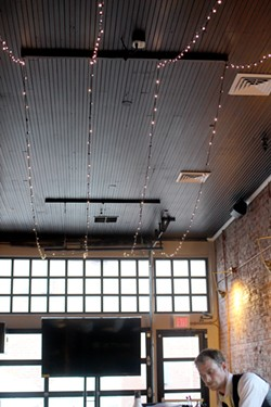 Large windows, an open floor plan and hanging lights set the mood at Highwire. - HEATHER HOCH