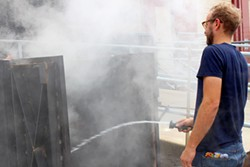 Distiller Nathan Thompson Avelino makes mesquite smoke to add character to the barley in the drying process. - HEATHER HOCH