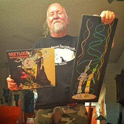 """Steve Purdy with his Greylock Mansion album cover and a trash-art piece he calls """"The Transmission People."""""""
